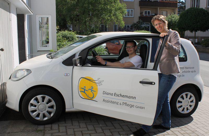 Geschäftsführerin Diana Escheman und Christopher von Studnitz mit einem Auto des Pflegedienstes